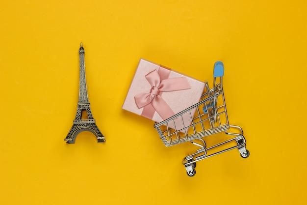 Confezione regalo con fiocco, statuetta della torre eiffel, carrello della spesa su sfondo giallo. shopping a parigi, souvenir