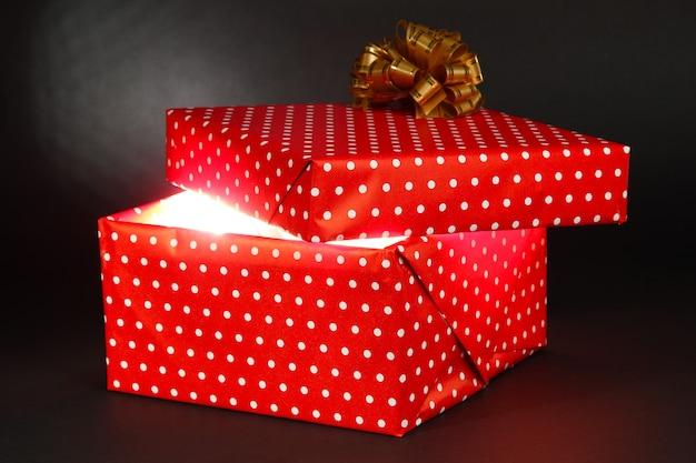 Confezione regalo con luce intensa su sfondo grigio scuro