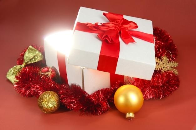 Confezione regalo con luce brillante su sfondo rosso
