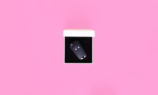 Confezione regalo con chiavi della macchina su sfondo rosa.piatto laico, vista dall'alto, copia spazio.concetto di auto, noleggio auto, regalo, lezioni di guida, patente di guida.