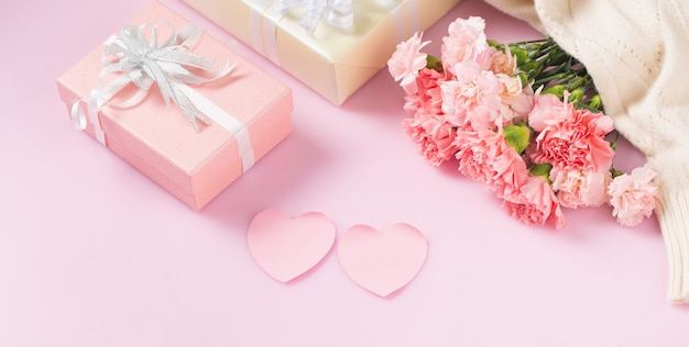 Confezione regalo con fiori di garofano, concetto di festa della mamma e san valentino