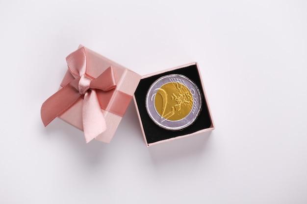 Confezione regalo con moneta su sfondo bianco