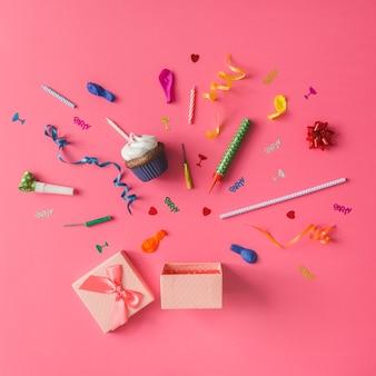 Confezione regalo con articoli per feste colorati sulla parete rosa. lay piatto.