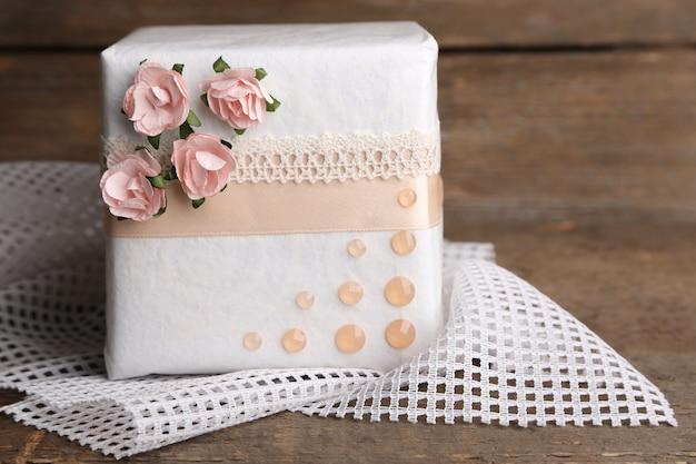 Confezione regalo con nastro colorato e fiori di carta su fondo in legno