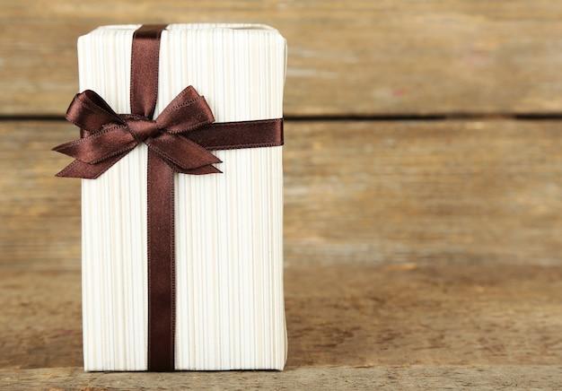 Confezione regalo con nastro colorato su superficie in legno