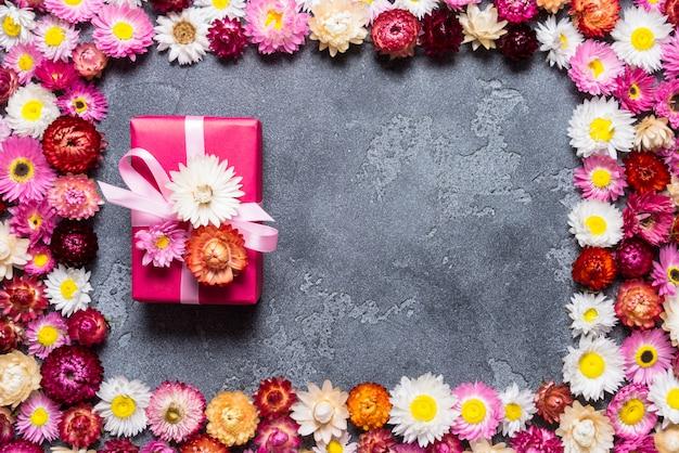 Confezione regalo con decorazioni floreali su sfondo grigio