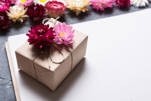 Confezione regalo con decorazioni floreali su fondo di carta