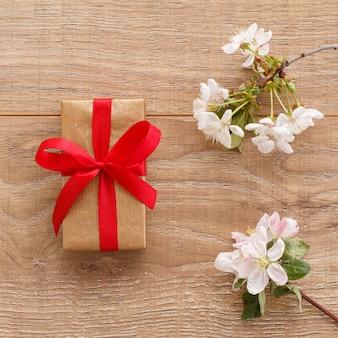 Confezione regalo con rami fioriti di ciliegi e meli sulla superficie in legno