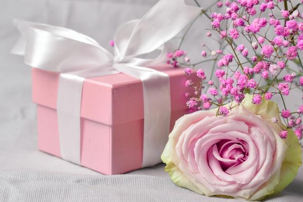 Confezione regalo con fiori su sfondo rosa di san valentino.
