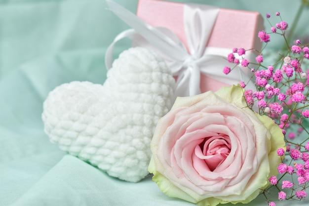 Confezione regalo con fiori e cuore in maglia di peluche bianco su sfondo rosa.