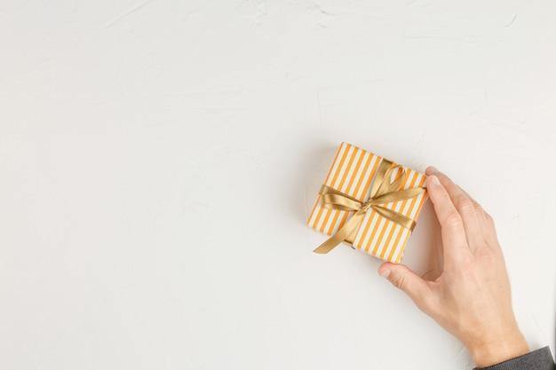 Confezione regalo con nastro dorato nelle mani su un muro bianco, vista dall'alto. lay piatto con copia spazio. lettera di congratulazioni con regali sul tavolo.