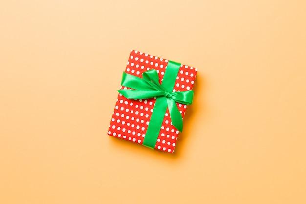 Confezione regalo con fiocco verde su sfondo arancione.