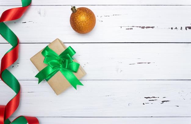 Confezione regalo con fiocco verde, nastro di raso e palla di natale