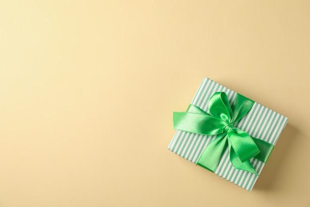 Contenitore di regalo con il nastro verde sul fondo di colore, sulla vista superiore e sullo spazio per testo