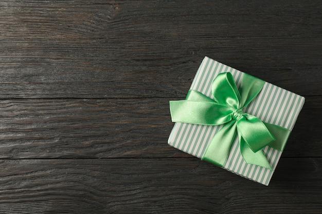 Contenitore di regalo con il nastro verde su fondo di legno, vista superiore e spazio per testo