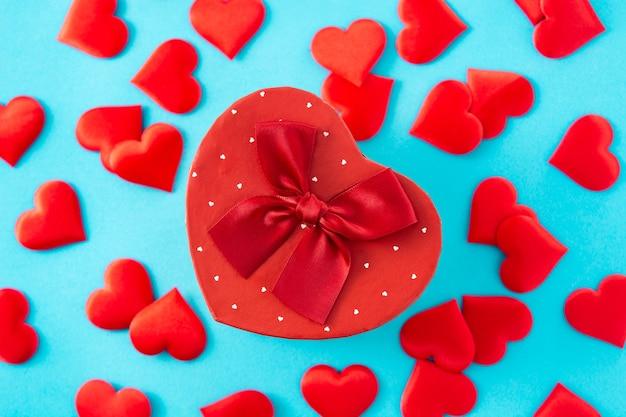 Confezione regalo a forma di cuore e cuori su sfondo blu.