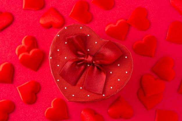 Confezione regalo a forma di cuore e cuori su sfondo rosso.