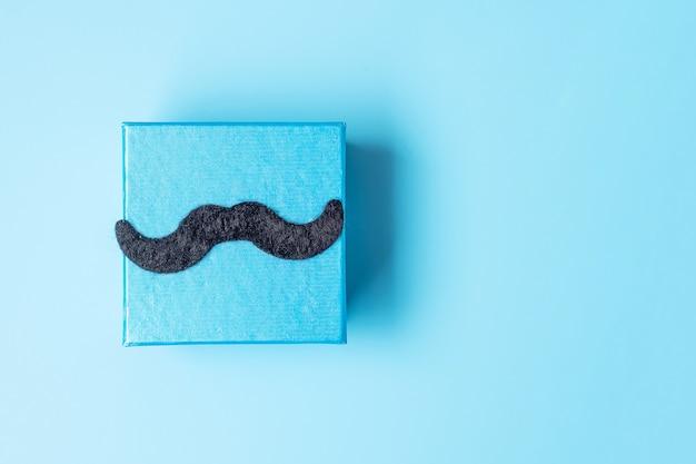 Confezione regalo con baffi su sfondo blu, preparazione per i padri. giornata mondiale degli uomini internazionali e concetto di festa del papà