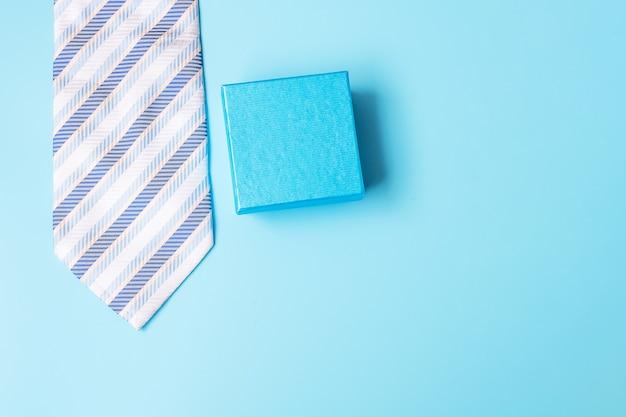 Confezione regalo con e cravatta su sfondo blu, preparazione per i padri. giornata mondiale degli uomini internazionali e concetto di festa del papà