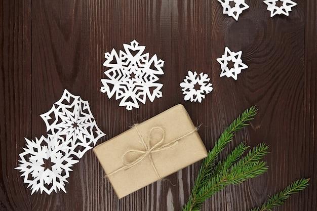 Confezione regalo con fiocchi di neve di carta e abete sulla tavola di legno