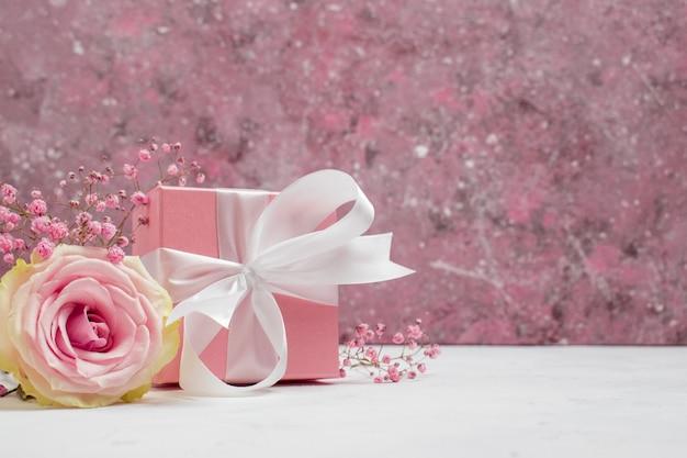 Confezione regalo con nastro rosa e sfondo gypsophila per san valentino