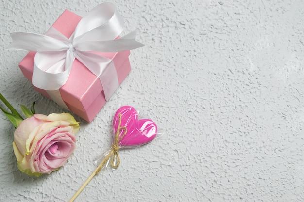 Confezione regalo con nastro rosa, lecca-lecca e gipsofila.