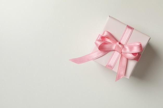 Confezione regalo con nastro rosa su sfondo bianco