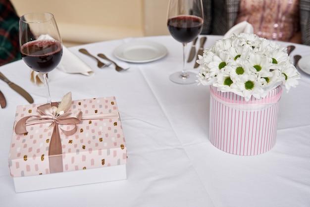 Confezione regalo con nastro rosa con fiori bianchi su tavolo bianco