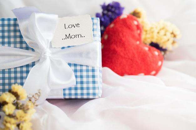 Confezione regalo con fiore viola, etichetta di carta con amore mamma e cuore rosso
