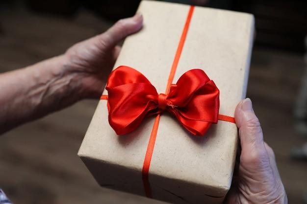Confezione regalo con fiocco rosso nelle mani della nonna macro