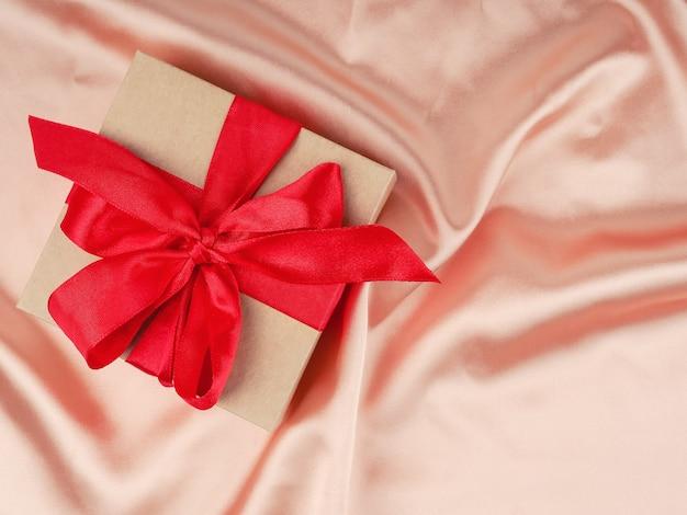 Confezione regalo con fiocco rosso, su uno sfondo di raso nudo, matrimonio e concetto di natale.