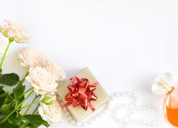 Confezione regalo con fiocco rosso, rose rosa, perline con bottiglia di profumo su bianco