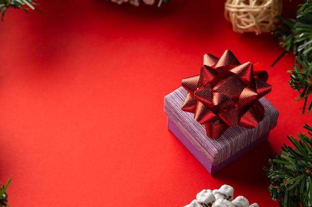 Confezione regalo con fiocco rosso su sfondo rosso tema di disimballaggio natalizio