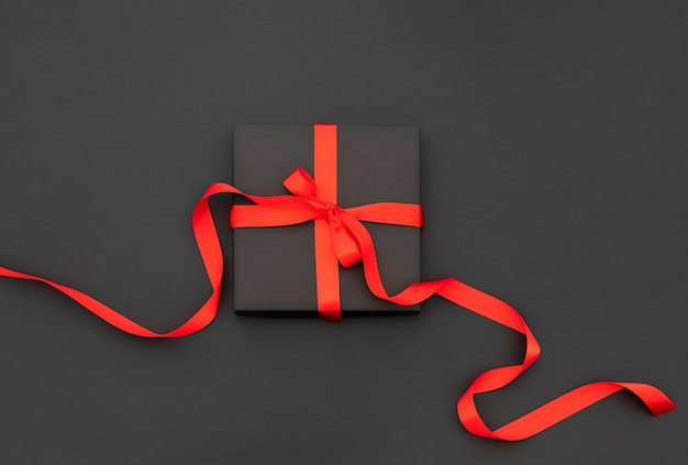 Confezione regalo con fiocco rosso e nastri.