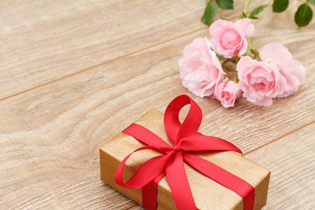 Confezione regalo con nastro rosso e bellissime rose rosa sulle tavole di legno. concetto di fare un regalo in qualsiasi festività. vista dall'alto.