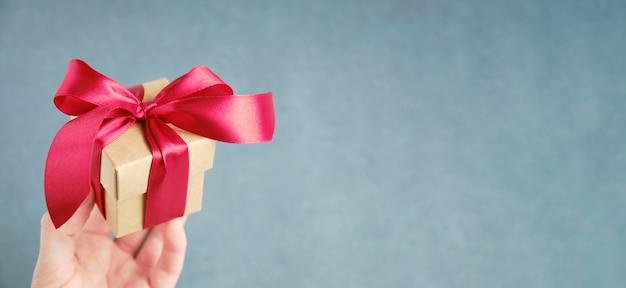 Confezione regalo con nastro rosso in mano su sfondo grigio, spazio per il testo