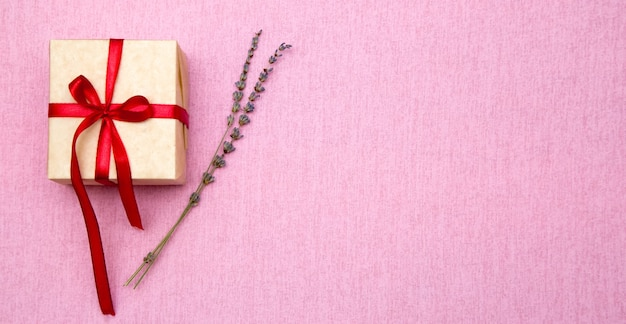 Confezione regalo con nastro rosso e rametti di lavanda. composizione festiva.