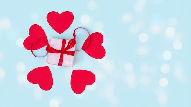 Confezione regalo con nastro rosso e cuori di amore di carta rossa intorno su sfondo blu con bokeh