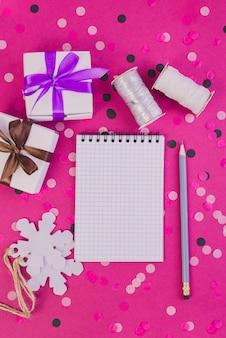 Confezione regalo con nastro e taccuino pulito con la matita sul tavolo rosa con coriandoli.