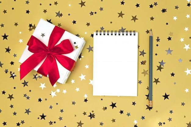 Confezione regalo con nastro e taccuino pulito con la matita sul tavolo giallo con coriandoli di stelle glitter.