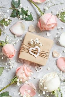 Confezione regalo con rose e piccoli fiori bianchi su sfondo grigio