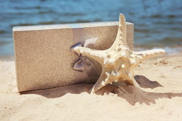 Confezione regalo con stella marina sulla spiaggia. concetto di vacanza estiva