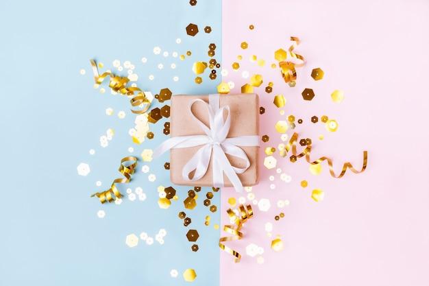 Confezione regalo con fiocco bianco su sfondo geometrico pastello scattering di lustrini esagonali dorati