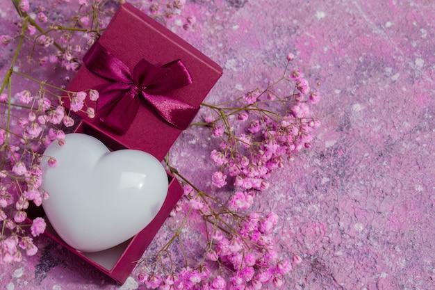 Confezione regalo con un cuore bianco su uno sfondo di fiori.