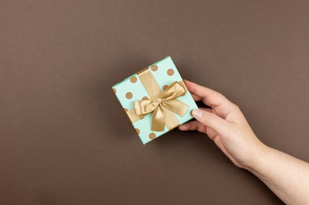Confezione regalo in mano di donna per evento festivo, mamma, san valentino, anniversario, natale, compleanno.