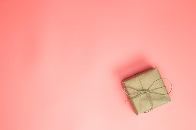 Confezione regalo avvolta in confezione regalo di carta marrone con rosa su sfondo rosa