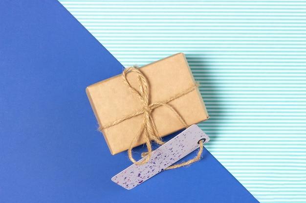 Confezione regalo avvolta in carta kraft su sfondo blu. vista dall'alto, concetto di vacanza.