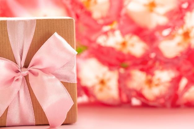 Confezione regalo avvolto con carta artigianale e fiocco rosa su sfondo di fiori rosa.