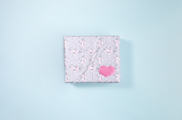 Confezione regalo avvolta in carta grigia con disegno floreale e cuore rosa. san valentino.