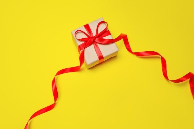 Regalo in una scatola su sfondo giallo, una composizione per la festa della mamma.